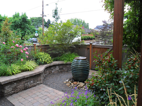 The soothing sound of water draws attention away from the nearby sidewalk in this small urban courtyard oasis. Installation by J. Walter Landscape & Irrigation Contractor.