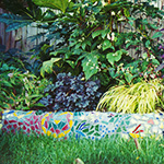 Detail of a mosaic wall and colorful plantings raised above the lawn in a small backyard.