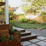 Edibles find a home in this small backyard with a deck and flow through planters for treating storm water.