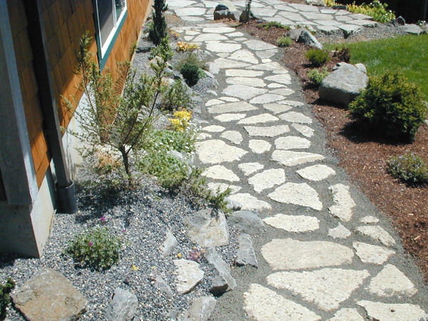 Reusing broken concrete from the old driveway keeps materials out of the waste stream and provides a permeable path alongside the wall of a new shop and alpine rockery top-dressed with gravel.