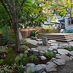 Japanese inspired stone placement creates a meditative atmosphere in this urban backyard.