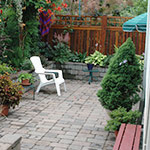 Creating a sunken garden with a living fence provided needed privacy in this small backyard on a corner lot.
