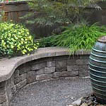 Planter boxes provide extra seating as well as a way to lift plantings up to viewing level in this small urban courtyard.  Spaces were defined with a mixture of hardscape materials.  A bubbling pot welcomes the birds as well as creating a sense of tranquility and it is low maintenance too.  Installation by J. Walter Landscape & Irrigation Contractor
